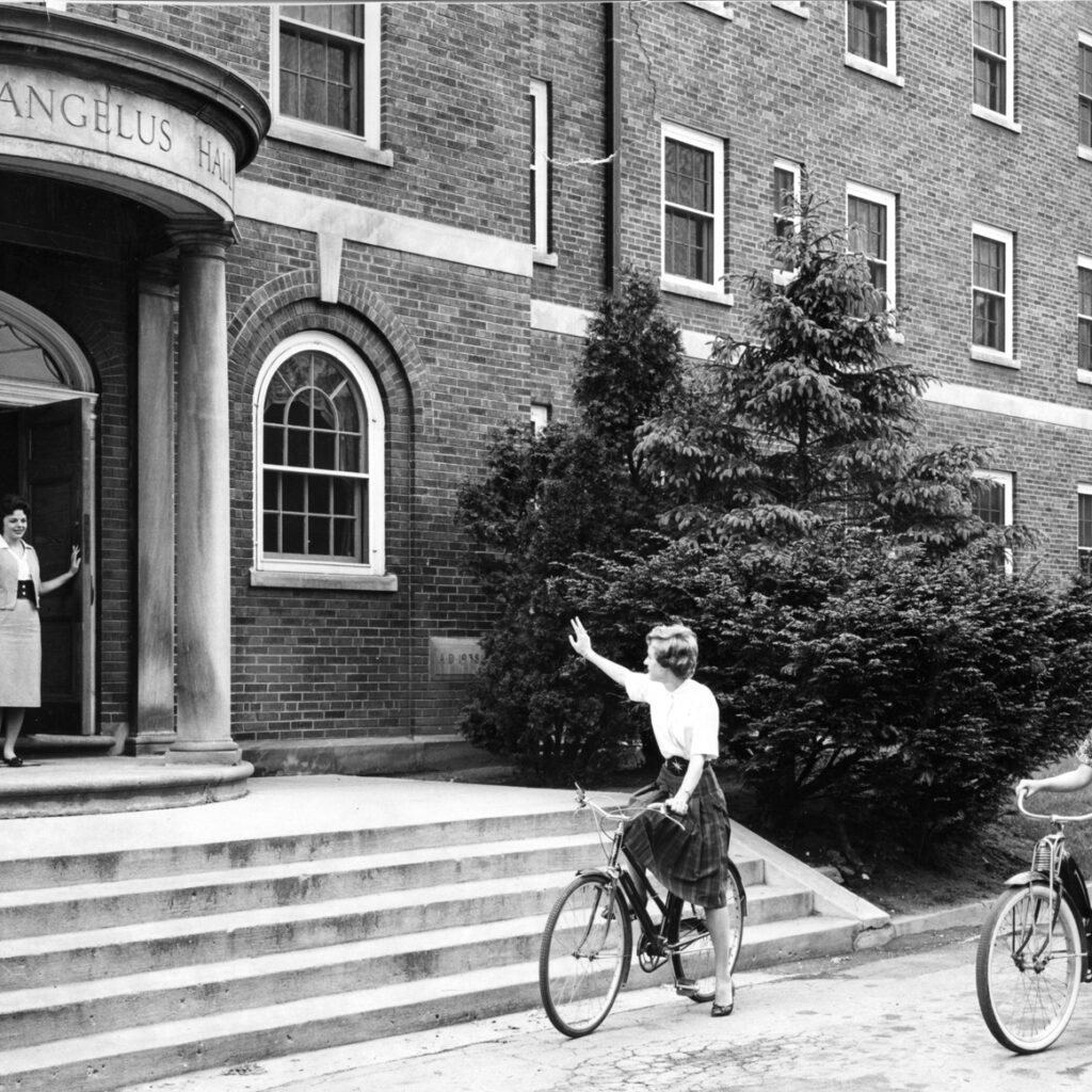 Students on bicycles outside Archangelus Hall 1950s,