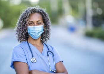 Portrait of an African American nurse wearing a protective face mask to avoid the transfer of germs during the COVID-19 outbreak.